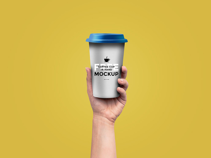 Coffee Cup In Hand Mockup by GraphicsFuel
